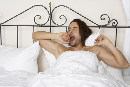 freeing: young man yawning in bed