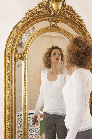formulate: woman applying lipstick in mirror