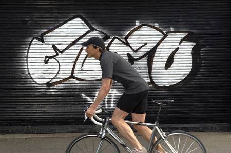 passtime: Male cyclist passing graffiti in street, side view LANG_EVOIMAGES