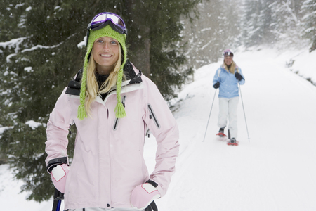 snowshoes: Young woman smiling on ski-slope, person in background on snow-shoes, portrait LANG_EVOIMAGES
