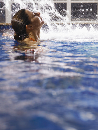 thirtysomething: Woman swimming in pool LANG_EVOIMAGES