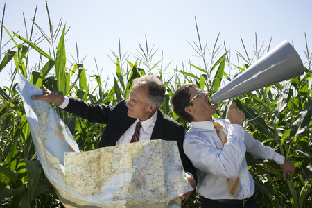 Businessmen in a cornfield with a map and megaphone.