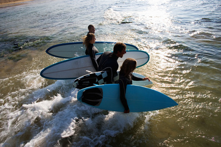 run down: Four people carrying surfboards into the water laughing.