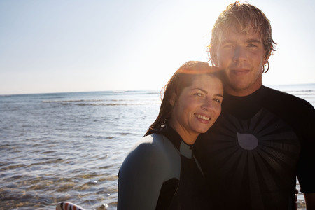 clear waters: Couple standing on beach with surfboard. LANG_EVOIMAGES