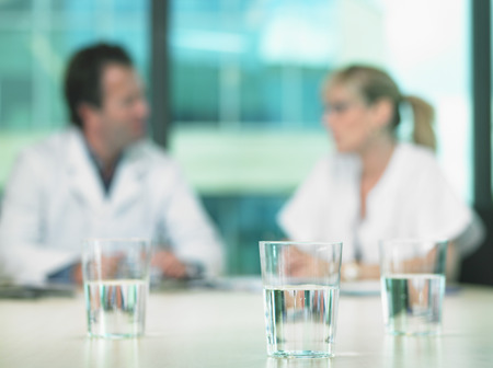 co: Two doctors in a business meeting. Out of focus. Close up on glasses of water in foreground.