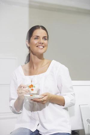 english ethnicity: Smiling woman sitting on desk drinking tea. LANG_EVOIMAGES