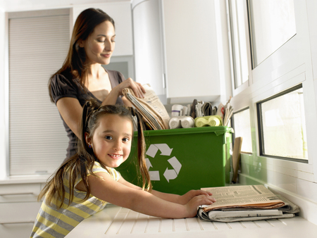 Girl (4-6) helping mother recycle newspapers, smiling, portrait LANG_EVOIMAGES