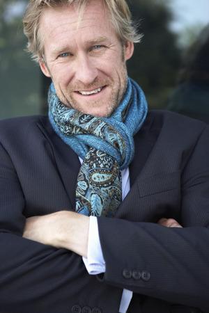 panache: Businessman wearing extravagant scarf leaning against window.
