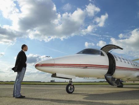 Businessman facing private jet on tarmac.