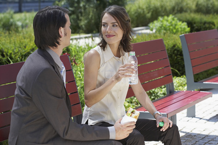 three persons only: businessman and woman looking at each other with lunch on a bench outdoors LANG_EVOIMAGES