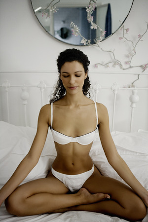 full length mirror: Woman doing yoga on bed. LANG_EVOIMAGES
