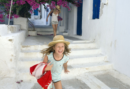 naxos: Woman and young girl running outside house smiling with towels. LANG_EVOIMAGES