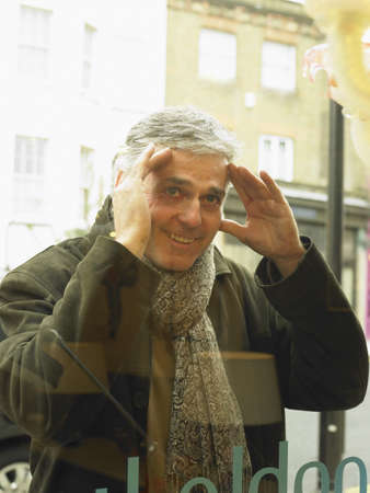 50 something: Mature man peering into shop window, smiling LANG_EVOIMAGES
