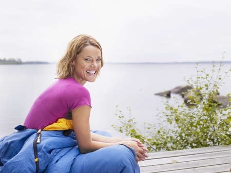three persons only: Woman with sleeping bag wrapped around her waist laughing by water.