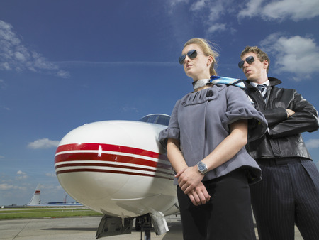 Pilot and flight attendant standing in front of private jet. LANG_EVOIMAGES