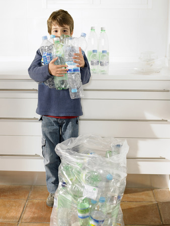 strive for: Young boy holding an armful of recyclable plastic bottles, portrait LANG_EVOIMAGES