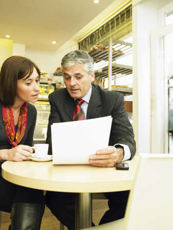 50 something: Businesswoman and man sitting in cafe looking at document LANG_EVOIMAGES