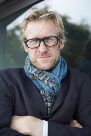 panache: Businessman wearing extravagant scarf leaning against window with glasses.