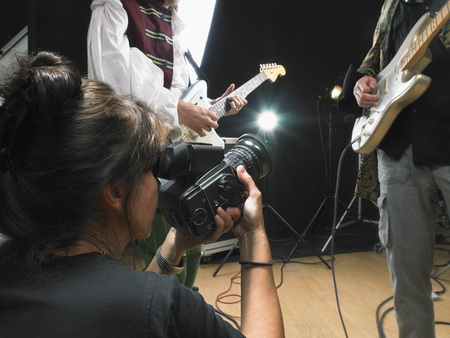 entertainers: Female photographer shooting two electric guitar players in studio close up. LANG_EVOIMAGES
