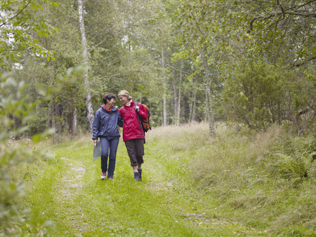 Two women walking through a forest with a map smiling.
