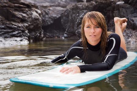 Woman lying on surfboard in the water.