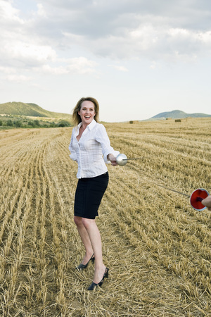 Businesswoman fencing in a wheat field.