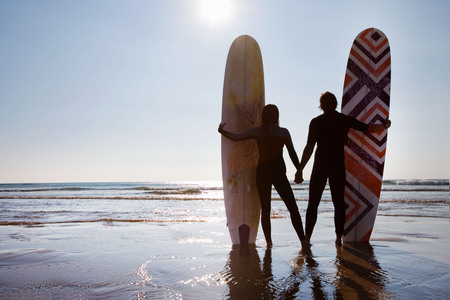blue waters: Couple standing on beach with surfboards holding hands.