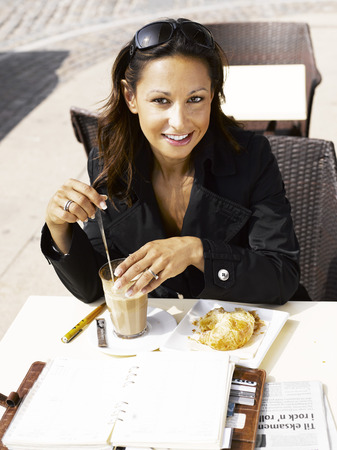 Woman stirring her drink at an outdoor restaurant