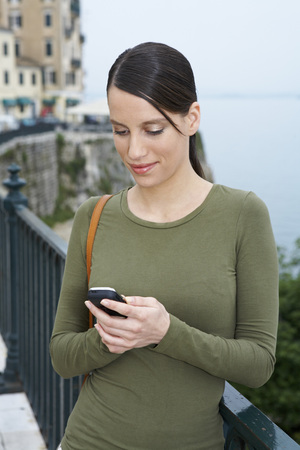 sidewalk talk: Young woman portrait with mobile looking at display smiling old city in background. LANG_EVOIMAGES