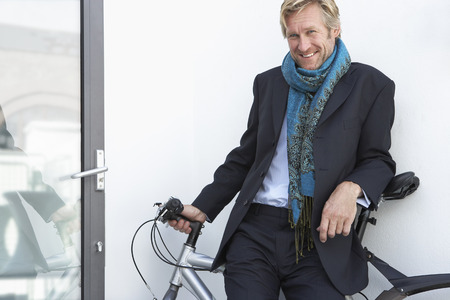 panache: Businessman wearing extravagant scarf with bicycle. LANG_EVOIMAGES