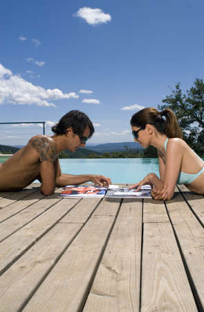 two piece swimsuit: Couple sunbathing by a swimming pool with magazines