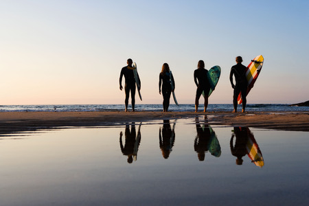 Four people standing on the beach with surfboards.