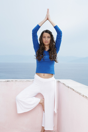 Young woman on balcony doing yoga sea and sky in background. LANG_EVOIMAGES