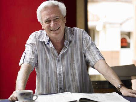 50 something: Senior man reading newspaper in café, smiling, portrait LANG_EVOIMAGES