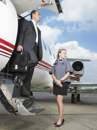 Businessman exiting private jet beside stewardess. LANG_EVOIMAGES