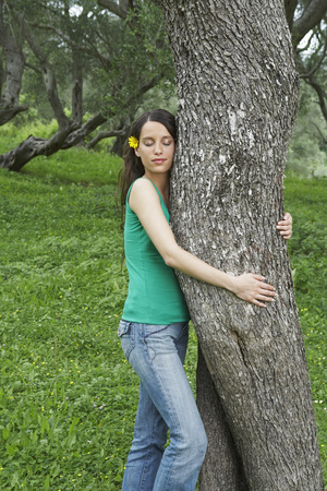 Young woman hugging tree in orchard with eyes closed.