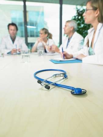 Business meeting of a group of doctors in a conference room around a table. Close up on stethoscope. LANG_EVOIMAGES