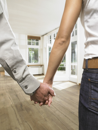 unoccupied: Close up on hands holding together of a couple in an empty house.