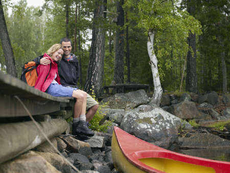 enjoys: Couple sitting on a dock near a boat laughing. LANG_EVOIMAGES