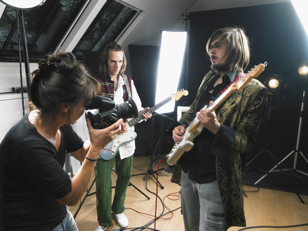 entertainers: Female photographer shooting two electric guitar players in studio.