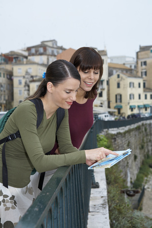 ruck sack: Two young women reading map smiling old city in background.