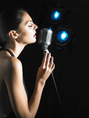 Woman singing into microphone. LANG_EVOIMAGES