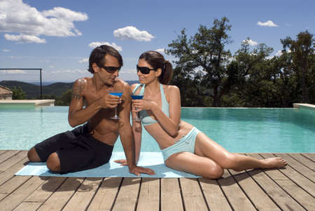 two piece swimsuit: Couple sunbathing by a swimming pool with drinks LANG_EVOIMAGES