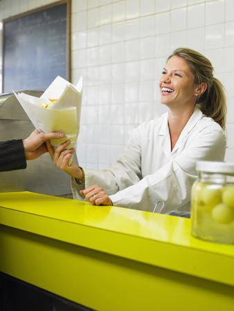 appearance: Young woman serving customer in fish and chip shop, smiling