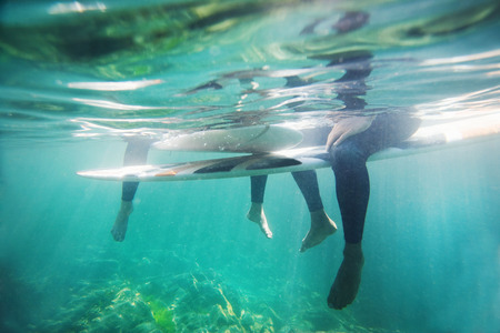 two persons only: Couples legs and surfboards underwater.
