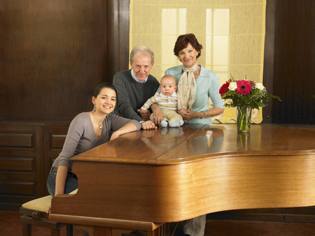 Multigenerational family (grandparents, mother and baby son (7months) by grand piano, portrait. Alicante, Spain.
