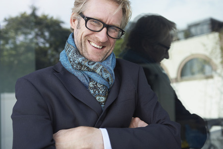 panache: Businessman wearing scarf leaning on a window. LANG_EVOIMAGES