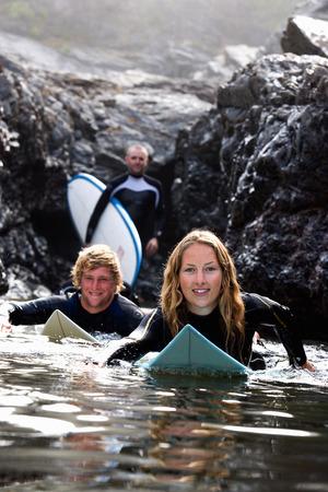 socializando: Tres personas con tablas de surf sonriendo.