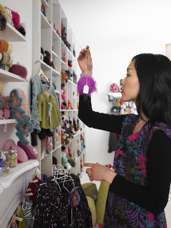 selections: Young woman choosing wool in craft shop, profile
