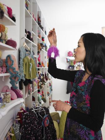 chose: Young woman choosing wool in craft shop, profile
